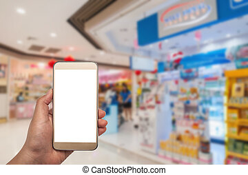 The women using smartphone in shopping mall on blurred...