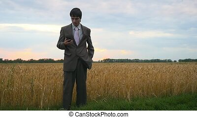 Businessman communicating on mobile phone in wheat field...
