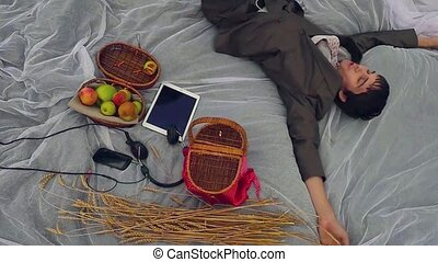 Young businessman lies on field on holiday near  headphones, mobile phone and tablet, top view in slowmotion. 1920x1080