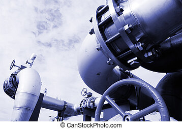 Pipes, bolts, valves against blue sky in blue tones