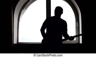 A silhouette of a bass guitar player on window background