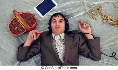 Businessman listening to music with headphones on wheat...