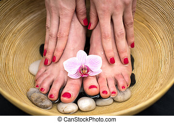 Female feet in spa bowl with sea salt, foot bath