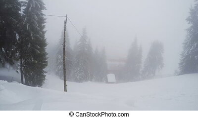 Snow storm in mountains - Wooden house near ski slopes in...