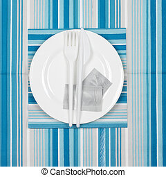 Disposable fast food set: white plate with condiment bags...