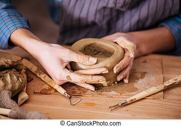 Clay pot making by hands of woman in pottery workshop -...