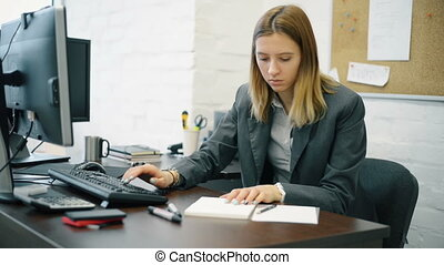 Portrait business woman at desk typing on computer