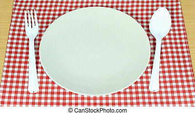 plate between spoon, fork on red tablecloth texture