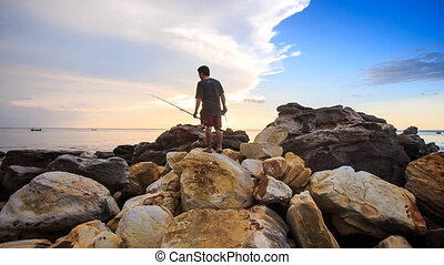 Closeup Backside Guy with Rods Walks on Stones to Sea at Sunset