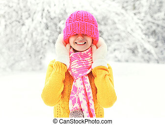 Happy smiling girl wearing a colorful knitted clothes having fun in winter day