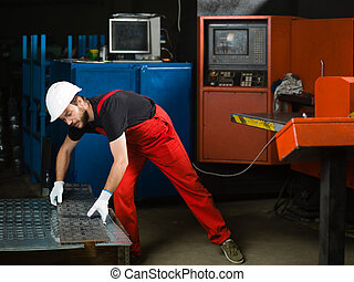 worker holding a sheet of metal plates