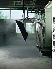 worker sand blasting a metal crate - view of a worker...
