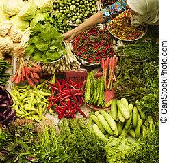 Vegetable market - Muslim woman selling fresh vegetables at...