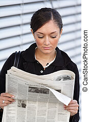Reading The Newspaper - A young handsome woman reads the...