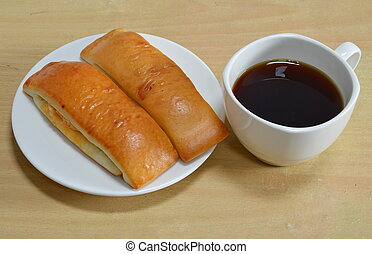bread stick and black coffee on desk