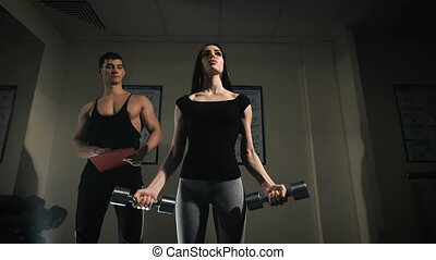 Trainer men are teaching woman lifting a dumbbell.