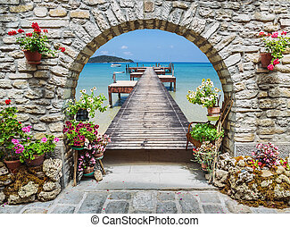 Seaview through the stone arch with flowers