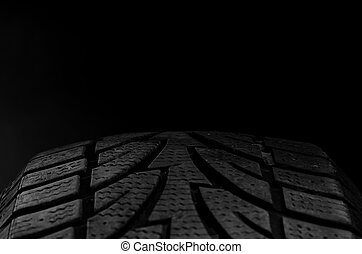 Tire tread - close up image of a tire on black