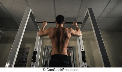 Back view portrait of a muscular man tightening in The Gym's...