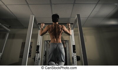 Back view portrait of a muscular man tightening in The Gyms...