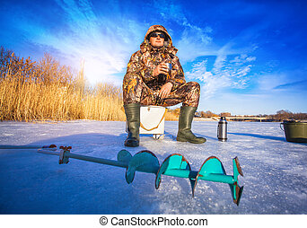Fisherman on a lake at winter sunny day