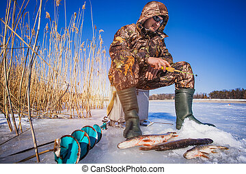 ice fisherman with pike caught on a tip up