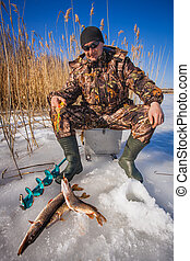 ice fisherman with pike caught on a tip up - Happy ice...