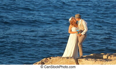 Wedding couple staying over beautiful landscape - Kissing...