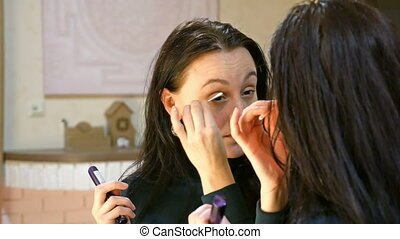 Pretty brunette woman applies make-up on her eyes
