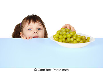 Child reaches for grapes lying on table