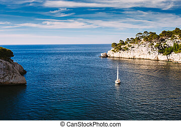 Yacht leaves from bay to open sea in Calanques on the azure...