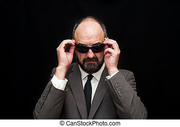 Handsome business man, bald and bearded, over black
