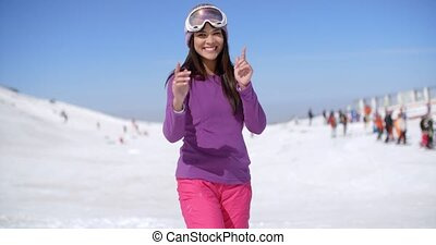 Happy young woman at a ski resort standing in the snow...