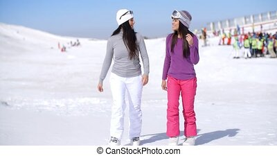 Two attractive young woman walking in fresh snow at a winter...