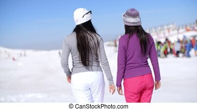 Two young woman walking in a winter ski resort - Two young...