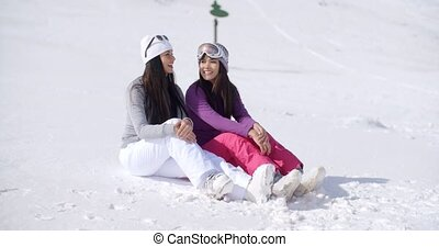 Two Friends Sitting Together on Sunny Ski Hill