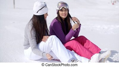 Two young women friends relaxing in the snow sitting side by...