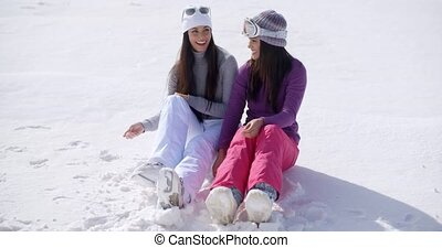 Two young women sitting chatting in the snow - Two young...