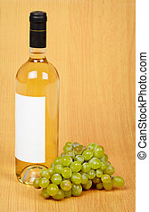 Still life - bottle of white wine and grapes on wooden surface