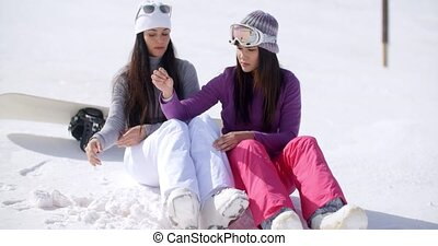Two young women sitting waiting in the snow with their...
