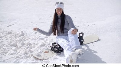 Attractive young woman sitting on her snowboard in fresh...