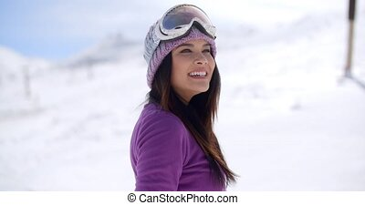 Happy beautiful young woman on a snowy mountain slope...