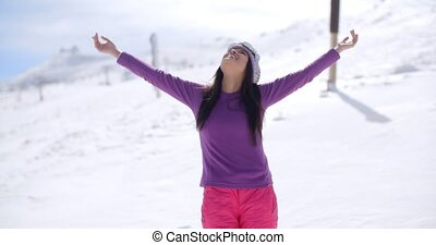Happy young woman embracing the winter sun standing with...