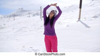Happy young woman celebrating her winter vacation standing...