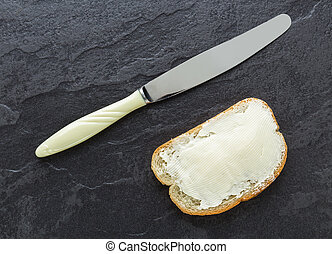 Sandwich, bread with butter and a knife on stone background...
