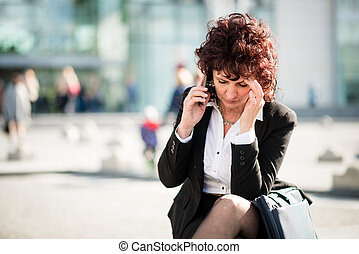 Mature business woman with phone in street