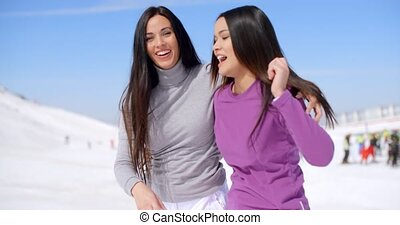 Laughing vivacious young women at a ski resort - Laughing...