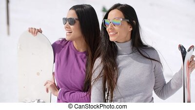 Two attractive young women with their snowboards standing...