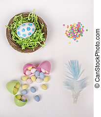 Easter eggs, basket, and candy on a white background