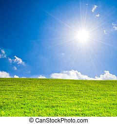 Global warming - Sunbeams under a blue sky over green grass